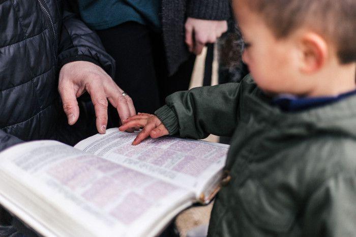 Uma criança apontando para um livro que um adulto segura.