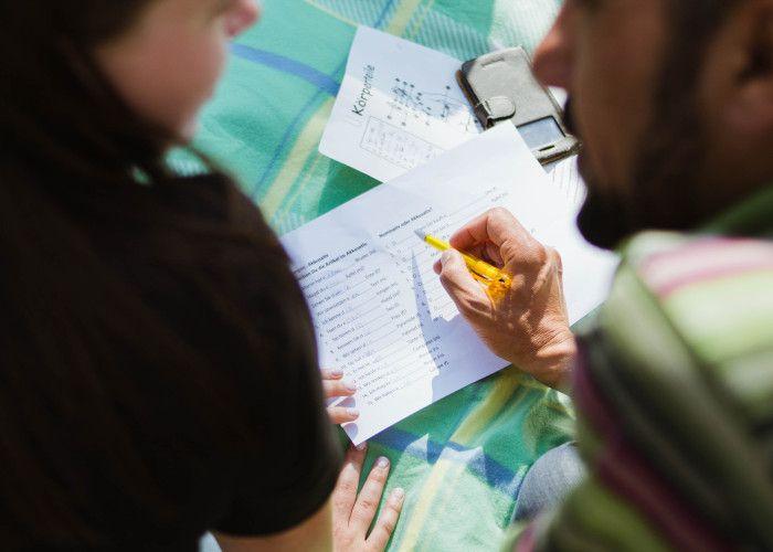 Homem apontando uma caneta para uma folha de anotações enquanto explica a uma colega.