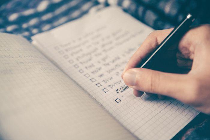 Mão masculina escrevendo em caderno quadriculado, fazendo uma lista.