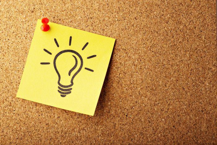 Nota autoadesiva amarela com uma lâmpada acesa iluminada fixada por um alfinete vermelho em um fundo marrom.