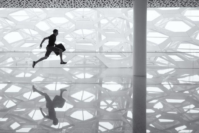 Homem correndo por uma espécie de salão moderno segurando uma pasta, em preto e branco.