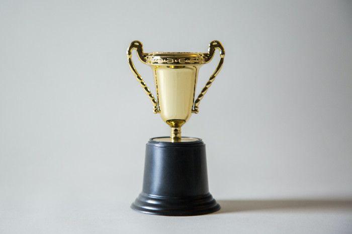 Troféu de ouro com a base preta em um fundo branco.