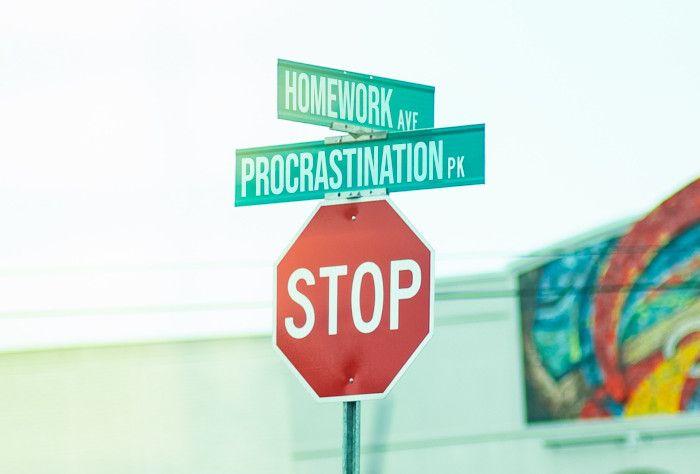 """Placa de rua escrita """"STOP"""" e logo acima duas placas menores indicando """"HOMEWORK"""" e """"PROCRASTINATION""""."""