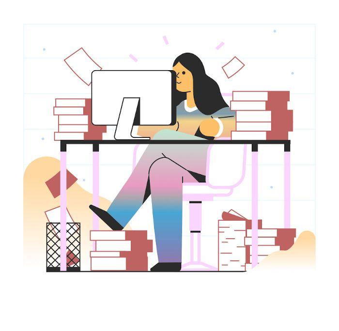 Mulher atrás de uma mesa com computador e vários livros concentrada.
