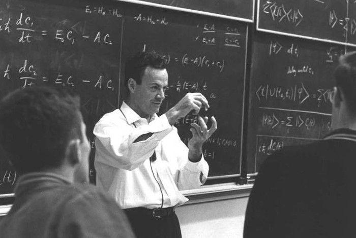 Richard Feynman lecionando física em uma sala de aula, gesticulando com as mãos.