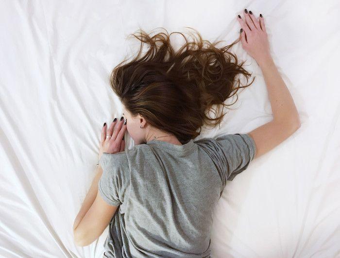 Mulher dormindo com os braços e cabelos esticados acima dos seus ombros.
