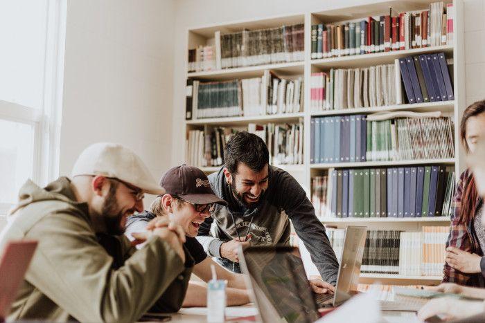 Três homens sentados diante de um computador, eles riem do que estão vendo.