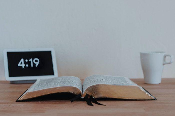 Livro sobre mesa marrom, com uma caneca branca e um relógio indicando quatro horas e dezenove minutos.