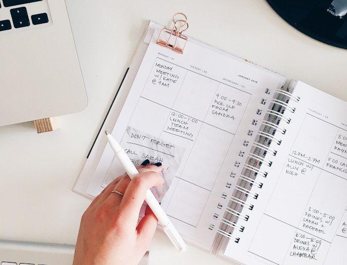 Agenda com anotações diárias e mão feminina colando lembrete e segurando caneta.
