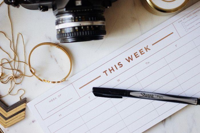 Planner semanal sobre uma mesa clara e uma canela apoiada sobre o planner.