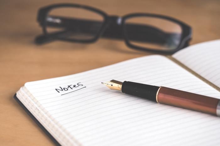 """Caderno sobre a mesa escrito """"notes"""", uma caneta disposta em cima do caderno e um óculos à mesa."""