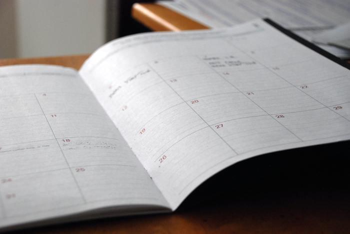 Agenda de papel sobre a mesa, imagem parcialmente desfocada, ficando visível apenas algumas datas.