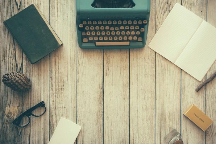 Mesa de madeira vista de cima com máquina de escrever, caderno aberto, caderno fechado, óculos e outros itens.