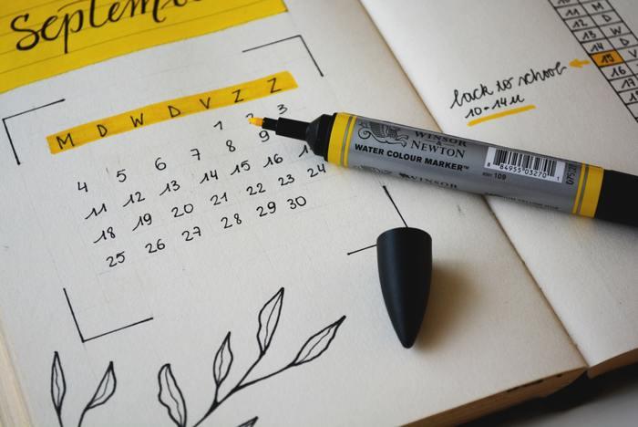 Agenda aberta no mês de setembro com algumas anotações e uma caneta amarela em cima da agenda.