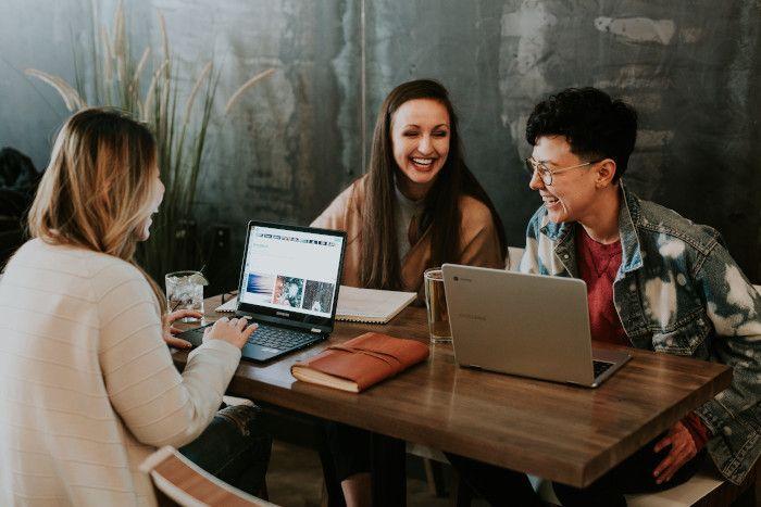 Três colegas sentadas ao redor de uma mesa com computadores. Elas estão rindo enquanto trabalham.