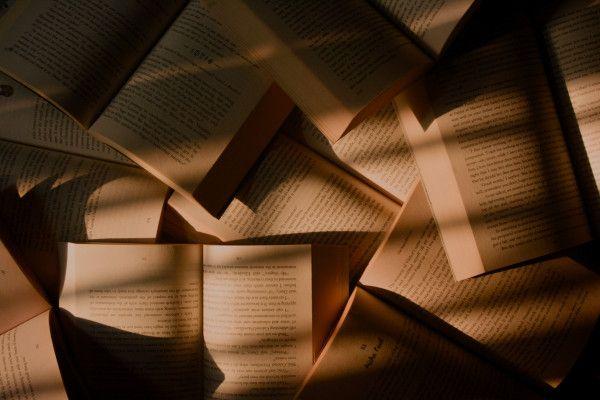 Vários livros sobrepostos à meia luz.