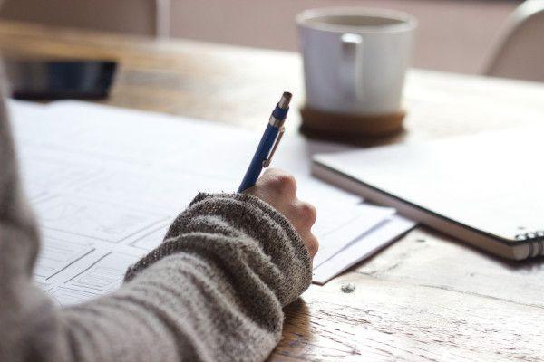 Mão com uma caneta escrevendo em um caderno, na mesa tem uma xícara de café.