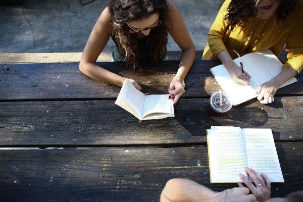 Três pessoas sentadas com livros estudando juntas.