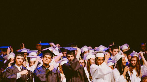 Acadêmicos na colação de grau com beca e chapéu.