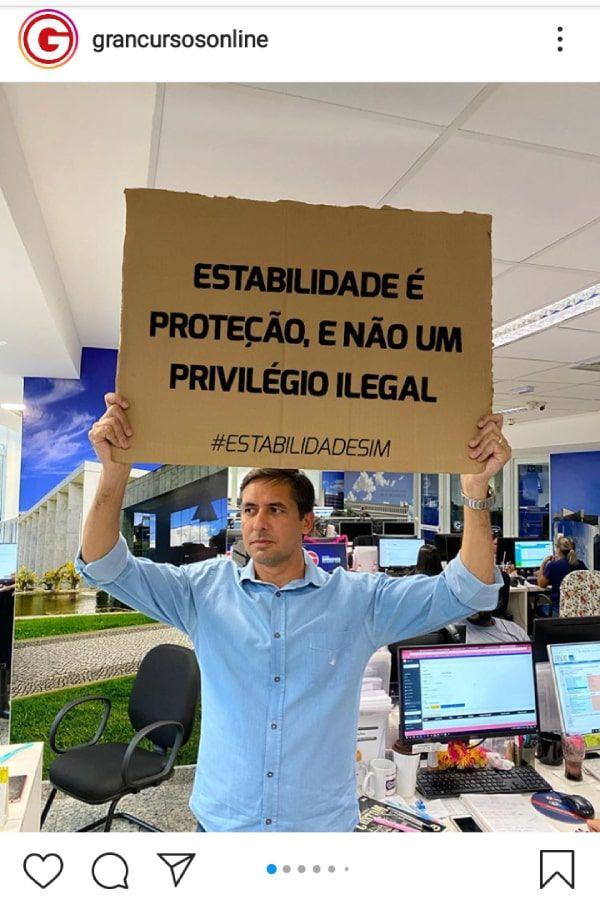 """Professor segurando placa: """"Estabilidade é proteção e não um privilégio legal!"""""""