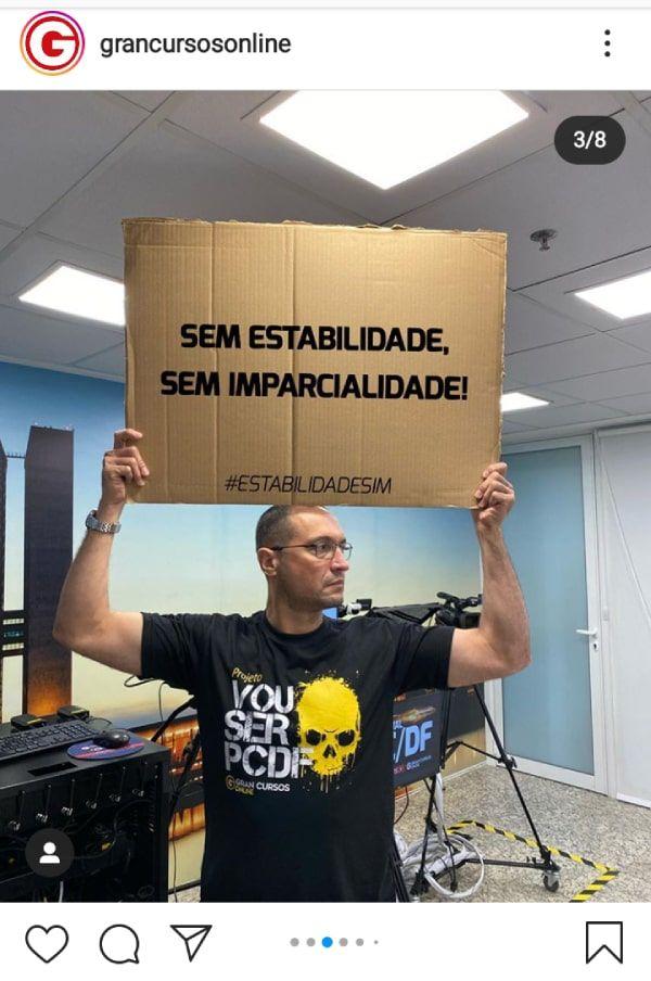 """Professor segurando placa que diz: """"Sem estabilidade, sem imparcialidade."""""""