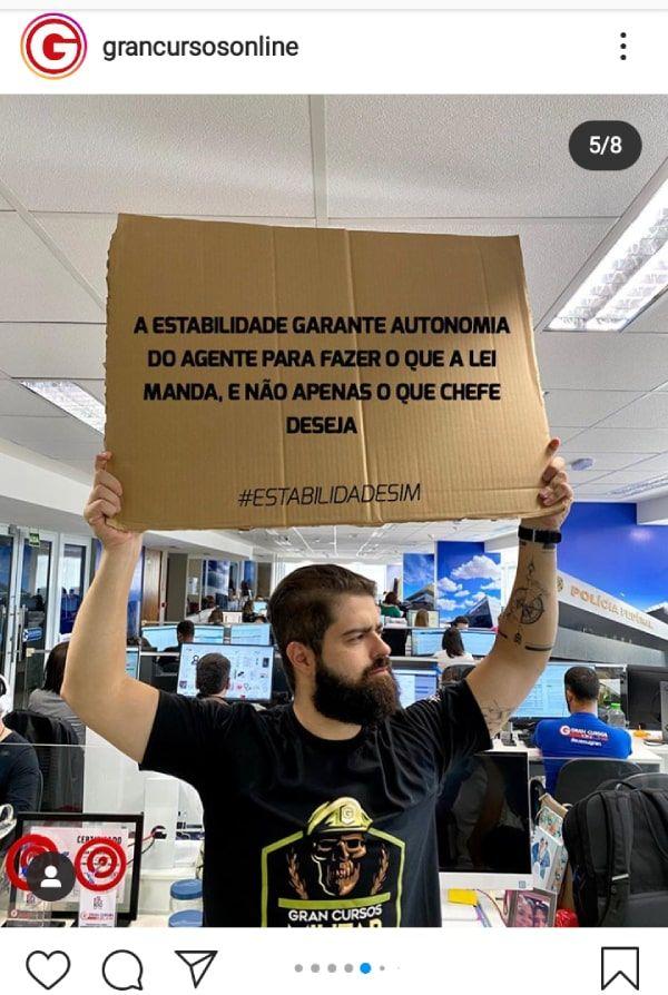 """Professor segurando placa que diz: """"A estabilidade garante autonomia do agente para fazer o que a lei manda, e não apenas o que chefe deseja"""""""