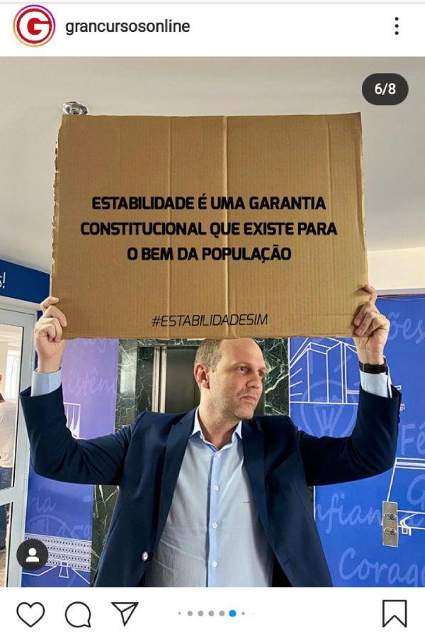 """Professor segurando placa que diz: """"Estabilidade é uma garantia constitucional que existe para o bem da população"""""""