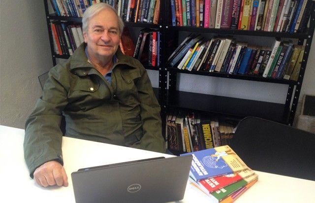 Foto do Professor Pier sentado em frente a uma estante de livros, vestindo uma jaqueta na cor verde militar com o computador posicionado à sua frente.