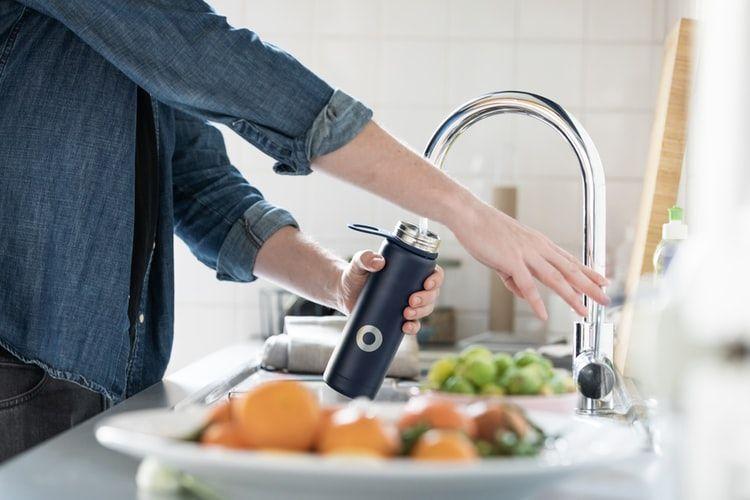 Homem enchendo garrafa de água na torneira. No balcão da pia, algumas verduras.