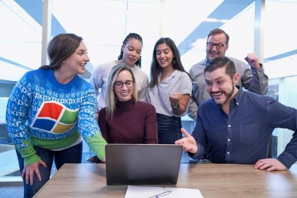 Foto de uma equipe ao redor de uma mesa com um notbook, todos olham para a tela e aparentam possuir competências para currículo
