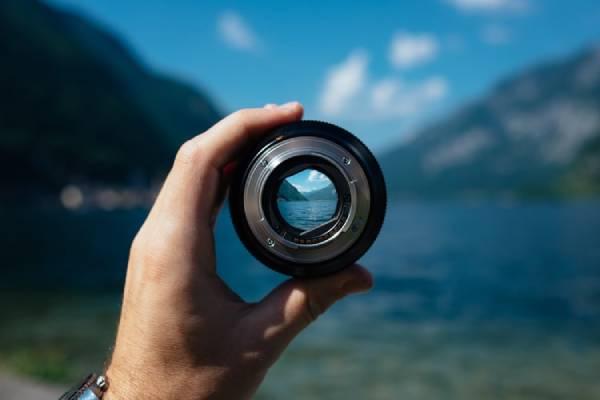 Mão masculina segurando uma lente focando numa paisagem ao longe