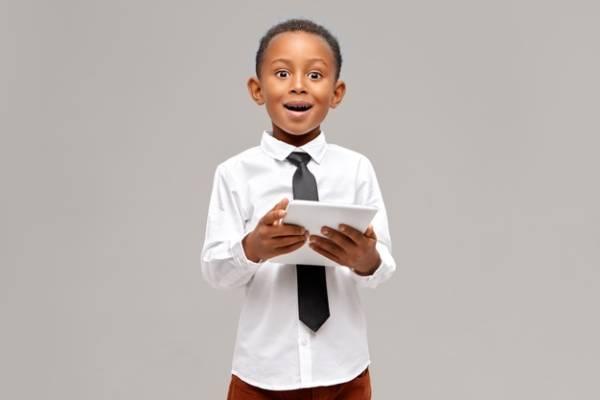 Menino negro segurando um tablet e com cara feliz, demonstrando ser um nativo digital